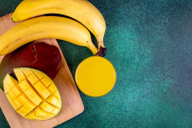 Mango affettato spazio della copia di vista superiore con le banane a bordo con succo d'arancia su verde