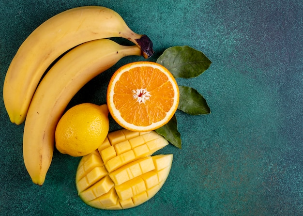 Top view copy space sliced mango with bananas half an orange and lemon on green