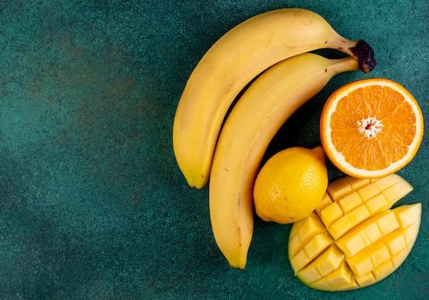 Vista dall'alto copia spazio affettato mango con banane mezza arancia e limone su verde
