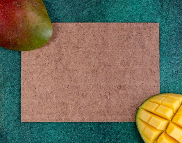 Top view copy space sliced mango with a cardboard insert on green