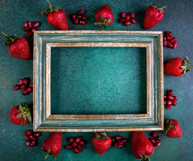 Top view copy space strawberries with peeled pomegranate around the frame on green