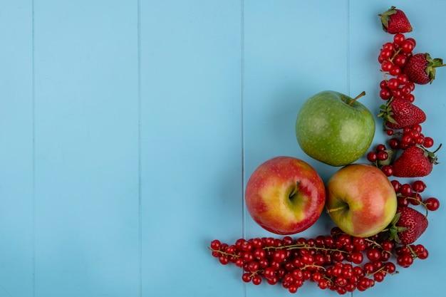 Вид сверху копия космической клубники с красной смородиной и яблоками на голубом фоне
