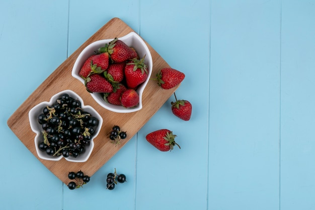 Top view copy space strawberry with black currants on a blackboard on a blue background