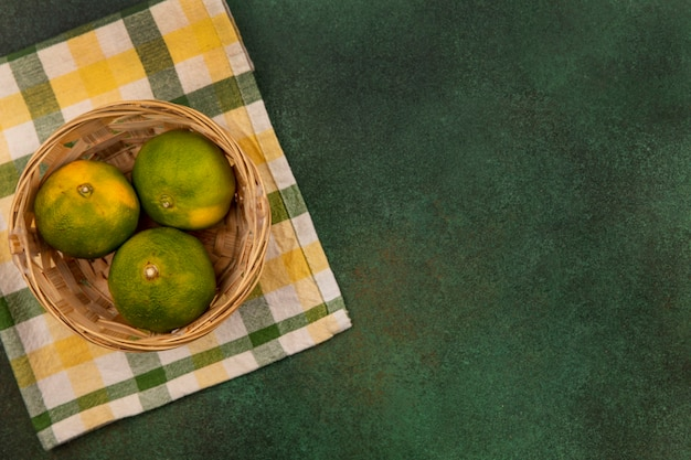 Top view copy space tangerines in a basket on a yellow-green checkered towel on a green wall