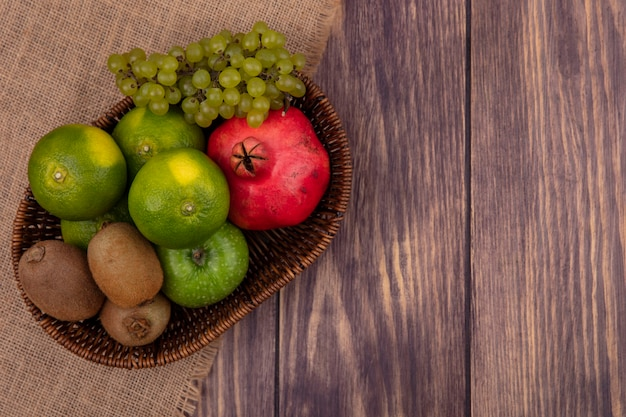 木製の壁にベージュのナプキンのバスケットにブドウキウイとザクロの上面コピースペースみかん