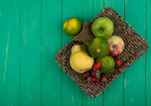 平面図のコピースペースみかんと緑の壁のバスケットに梨リンゴとイチゴ