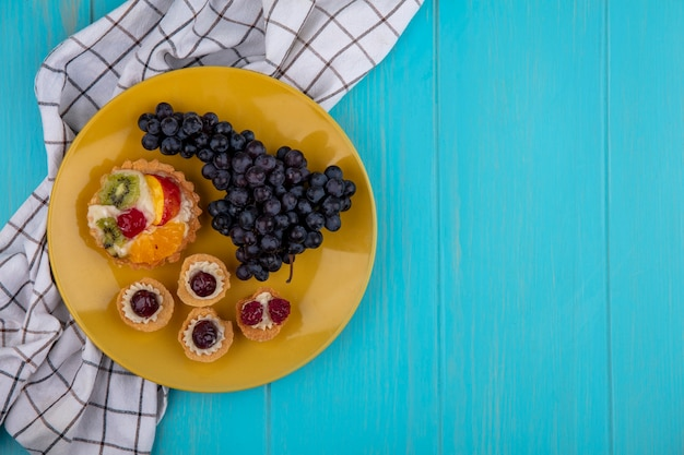 Top view  copy space tartlets with black grapes on a yellow plate  with a checkered towel on a turquoise background