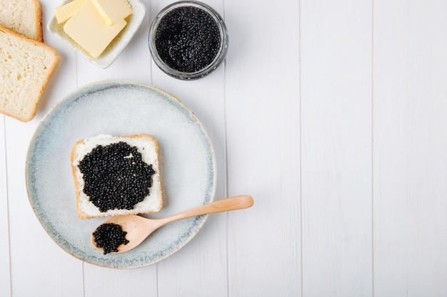 Top view copy space toast with black caviar on a plate with a spoon and butter with a can of black caviar on a white background