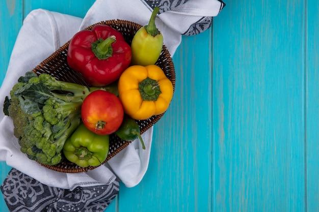 ターコイズブルーの背景にキッチンタオルの上のバスケットにキュウリとブロッコリーとピーマンの上面コピースペーストマト
