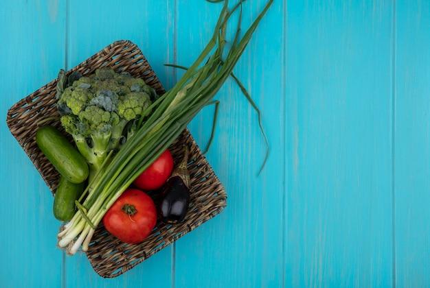 ターコイズブルーの背景のスタンドにキュウリネギブロッコリーと黒ナスとトップビューコピースペーストマト