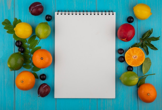 Top view  copy space white notepad with oranges  cherry plums  lemons  limes and plums on a turquoise background