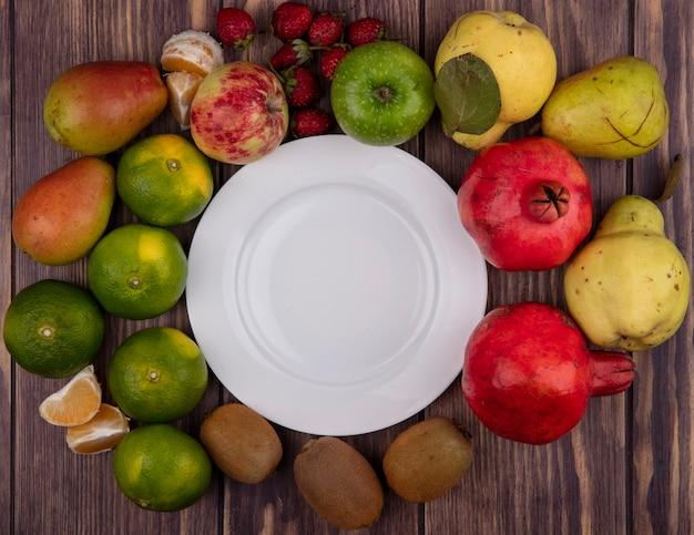上面図コピースペース木製の壁にキウイみかん梨イチゴとザクロと白いプレート
