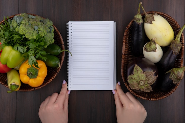 Top view copy space woman holding quaderno con peperoni prezzemolo e pomodori in un cesto di melanzane su fondo in legno