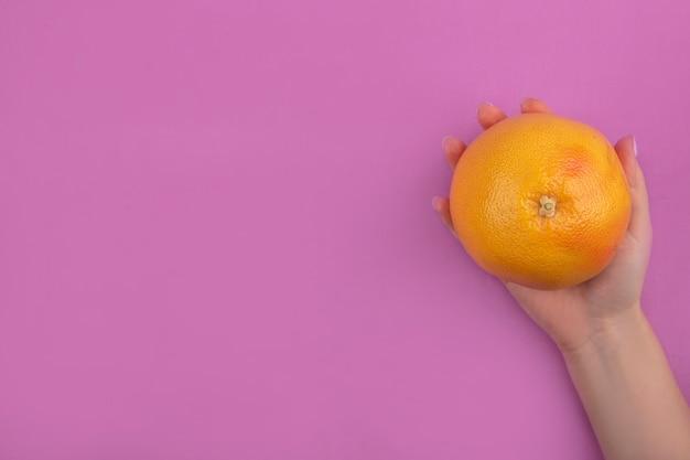 上面図コピースペースの女性はピンクの背景にグレープフルーツを手に持っています