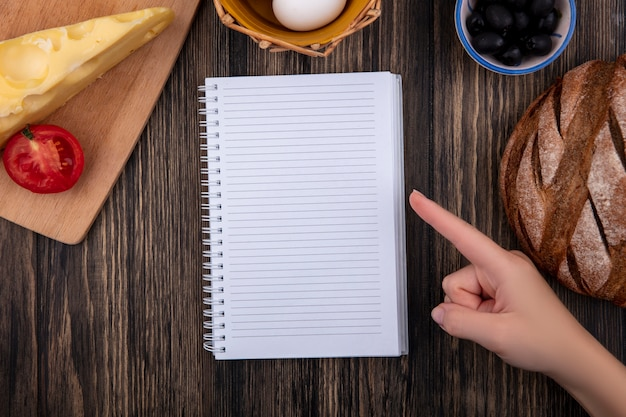 Top view  copy space  woman points to copybook with black olives with tomato  black bread and cheese on wooden background