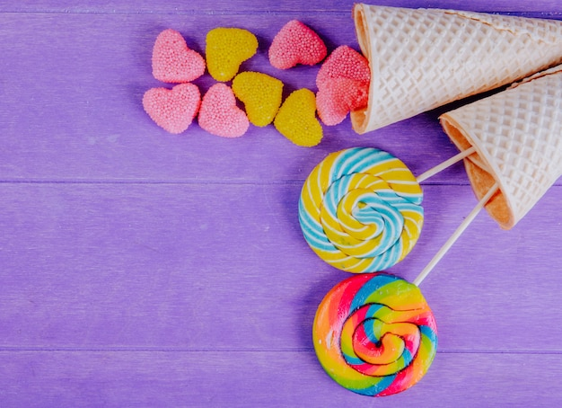 Top view copy space yellow and pink marmalade in the shape of a heart with colored icicles in waffle cones on a purple background