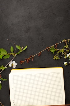 Тетрадь вида сверху вместе с цветами на темном столе