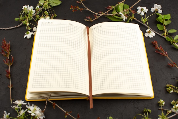 Top view copybook along with white flowers on the dark desk