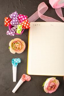 Un quaderno con vista dall'alto e fiori sul colore della pianta del fiore della scrivania scura