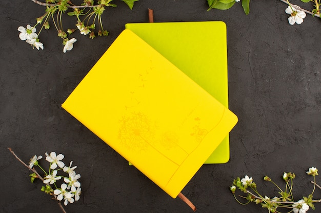 Top view copybooks yellow and mustard colored around white flowers on the dark floor