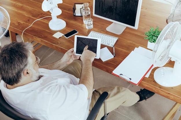 상위 뷰, copyspace입니다. 사업가, 컴퓨터와 팬이 있는 사무실의 관리자, 더위를 식히고 있습니다. 팬을 사용하지만 여전히 캐비닛의 불편한 기후로 고통 받고 있습니다. 여름, 사무실 작업, 비즈니스.