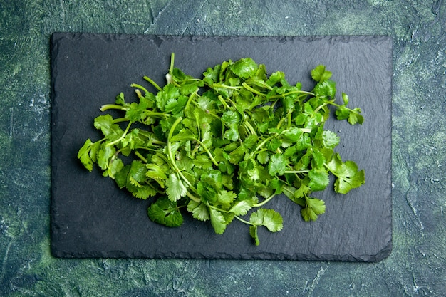 Top view of coriander bundle on wooden cutting board on green black mixed colors background with free space