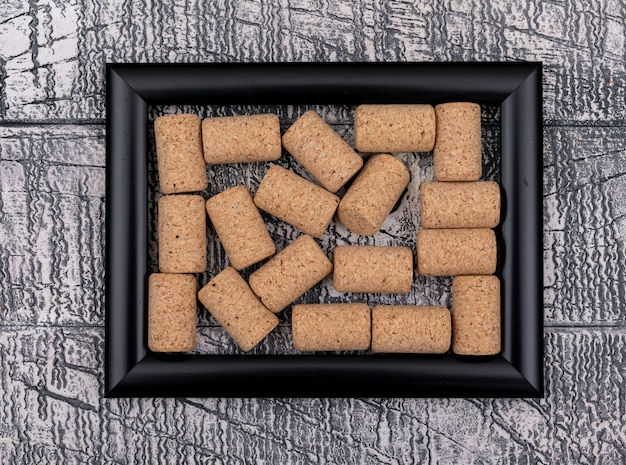 Top view of cork stoppers in black frame on white stone  horizontal
