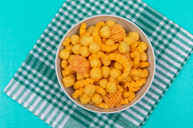Top view of corn balls in bowl on napkin and blue  horizontal