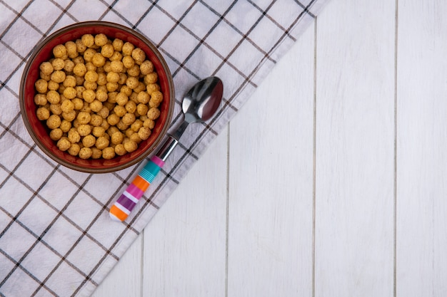 Top view of corn balls in a bowl with a colored spoon on a checkered towel on a white surface