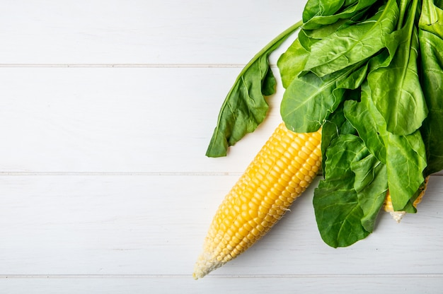 Top view of corn cob and spinach on wooden surface with copy space