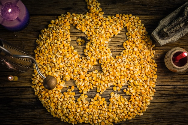 Top view corn kernels arranged in a halloween mask. on old wooden table