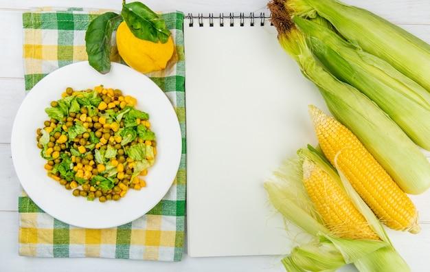 Vista superiore dell'insalata di mais sul panno e limone con pannocchie di mais e blocco note su superficie di legno