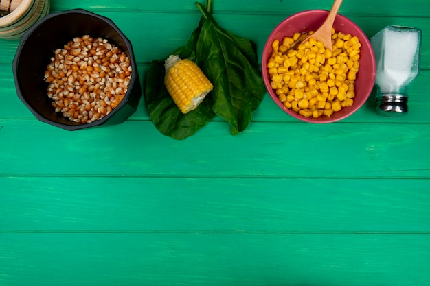 Top view of corn seeds with cut corn salt and spinach on green with copy space