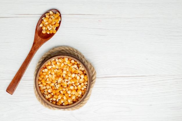 Giallo dei semi del cereale di vista superiore colorato su bianco