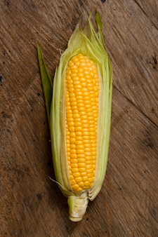 Top view corn with wooden background