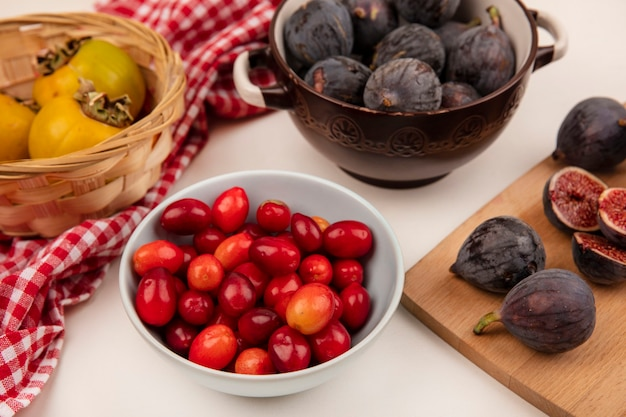 Top view of cornelian cherries on a bowl with black mission figs on a wooden kitchen board on a white wall