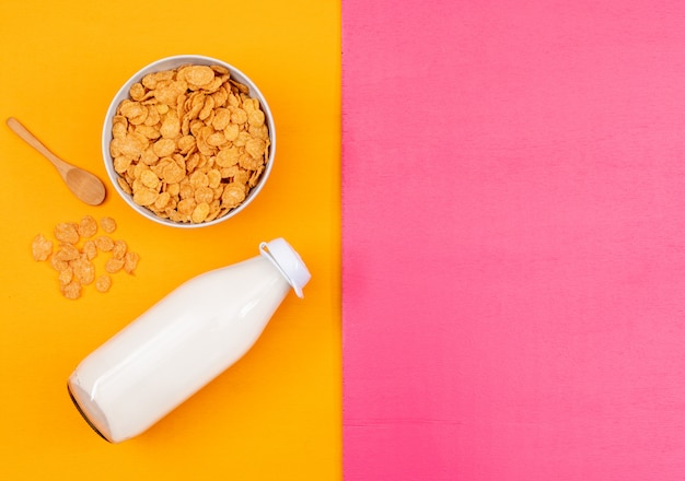 Top view of cornflakes and milk with copy space on pink and yellow background horizontal