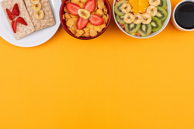Top view of cornflakes with fruits with copy space on yellow background horizontal