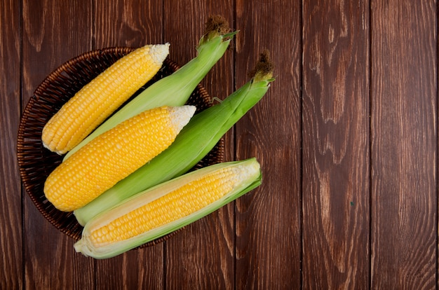 Top view of corns in basket on wooden surface with copy space