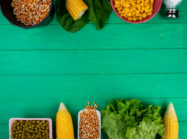 Top view of corns and corn seeds with green peas salt lettuce spinach on green surface with copy space