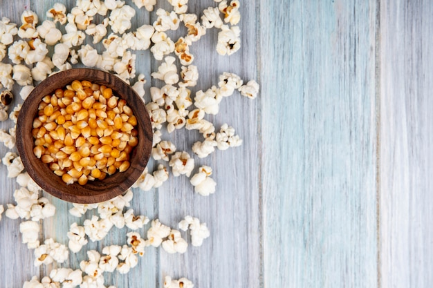 Top view of corns on wooden bowl with popcorn isolated on grey with copy space