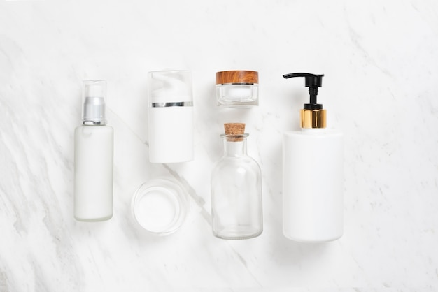 Top view of cosmetic bottles on white marble.