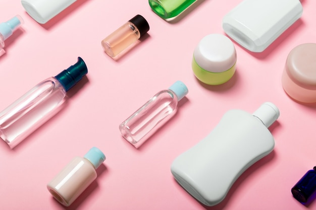 Top view of cosmetic containers, sprays, jars and bottles on pink . close-up view with empty space r