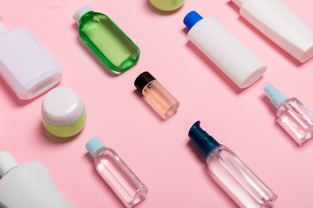 Top view of cosmetic containers, sprays, jars and bottles on pink . close-up view
