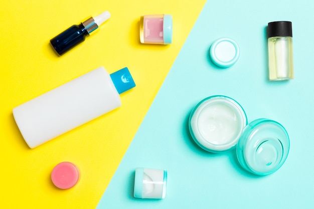 Top view of cosmetic containers, sprays, jars and bottles on yellow and blue background. close-up view with empty space for your design.