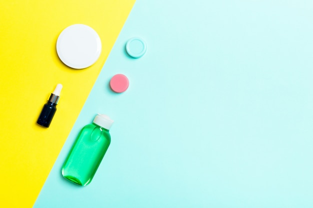 Top view of cosmetic containers, sprays, jars and bottles on yellow and blue background