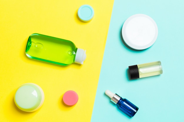 Top view of cosmetic containers, sprays, jars and bottles on yellow and blue background.