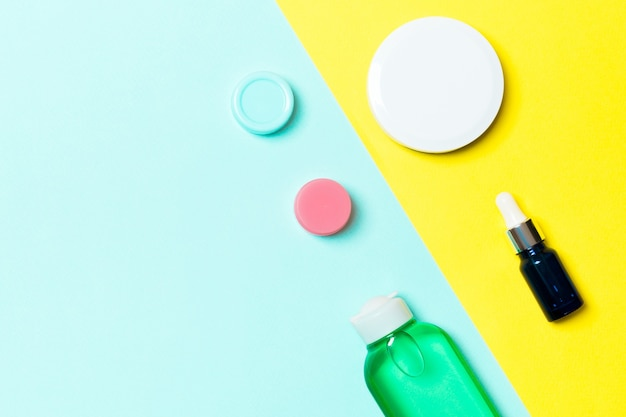 Top view of cosmetic containers on yellow and blue background Premium Photo