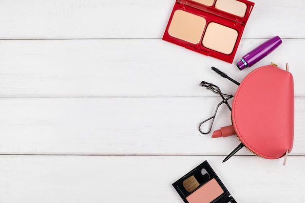 Top view of cosmetic items on white wooden table