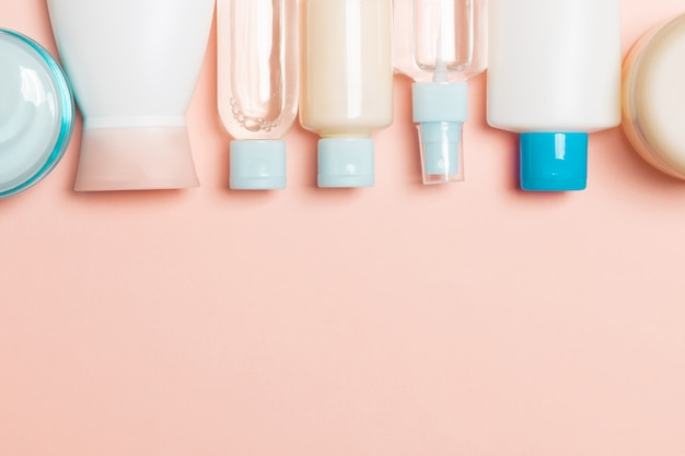 Top view of cosmetics bottles on pink background